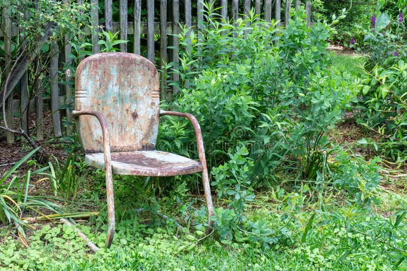 Empty old, weathered chair against a slat fence and greenery, aging death and grief concept. Horizontal aspect royalty free stock images