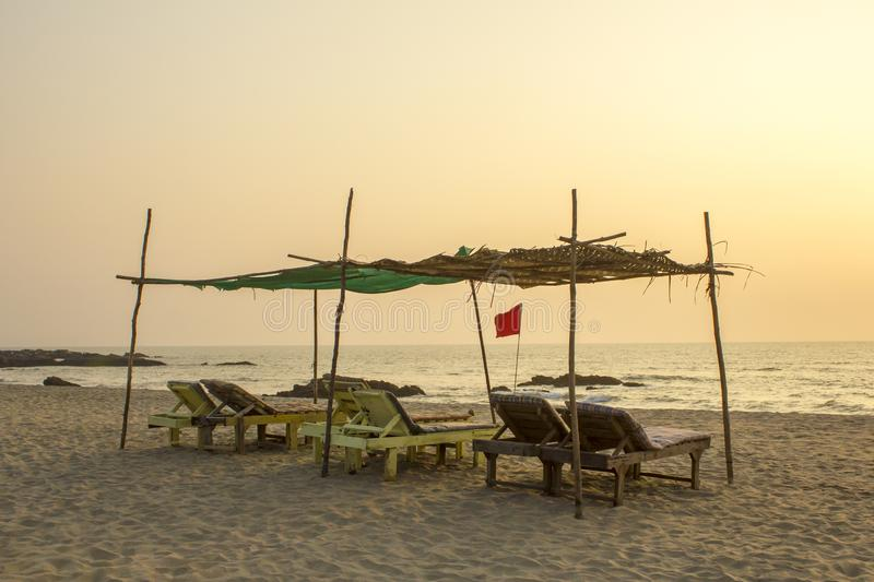 A empty old wooden beach loungers under a palm canopy on the sandy beach of the ocean in the evening. red flag on the sea coast stock image