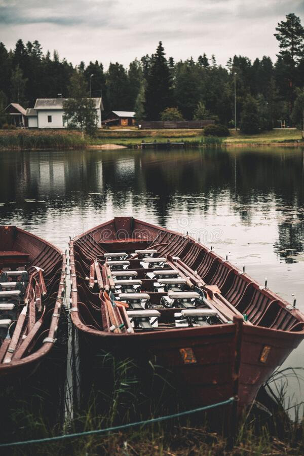 Empty wooden canoe boats on lake shore near building and pine forest in autumn. stock photography