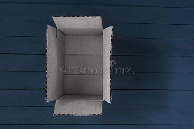 Empty open cardboard box on black wooden background. Delivery concept. Top view royalty free stock photos