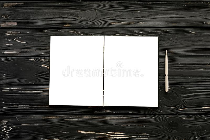 Empty open notebook and silver pen on the black wooden background. Horizontal. Top view royalty free stock images