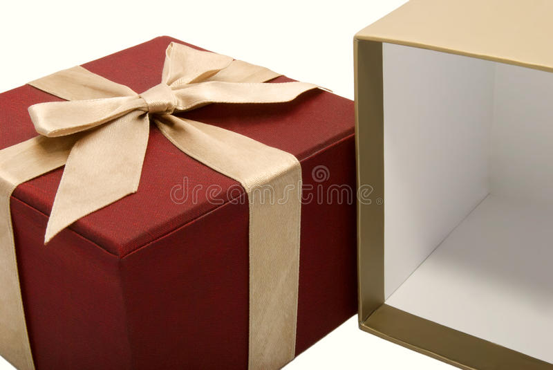 Empty opened gift box with a ribbon background. Empty opened wine color gift box with a gold ribbon background stock image