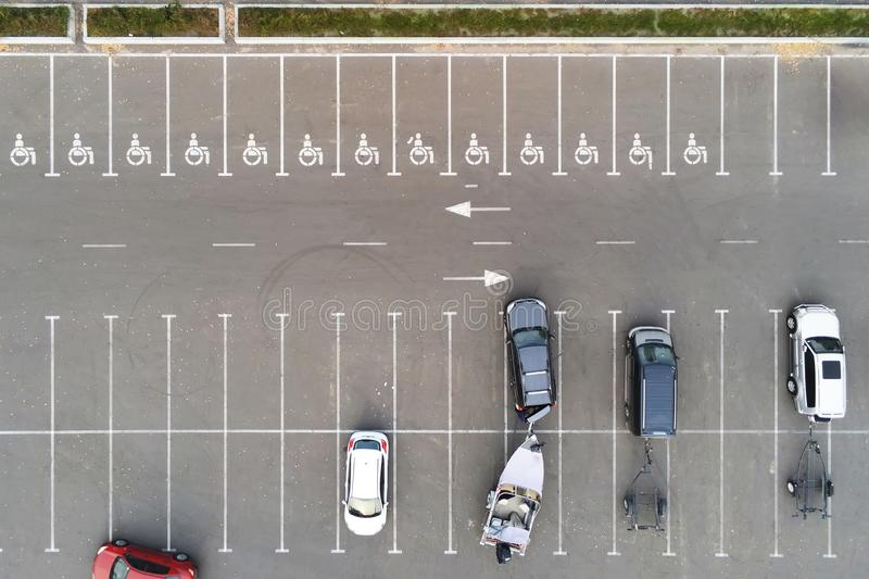 Almost empty outdoor car parking with handicapped symbol icon. Prking places reserved for disabled person. Aerial drone royalty free stock photos