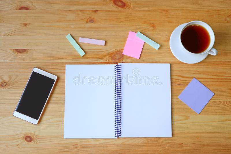 Empty pages opened notebook, smartphone, memo pad paper and a cup of hot tea on wooden working desk. Texture Background beige beverage black blank brown stock images