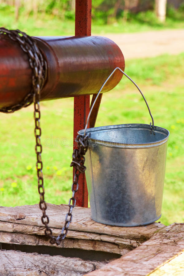 Empty pail, chain and well pulley. Empty pail, old chain and old well pulley royalty free stock images