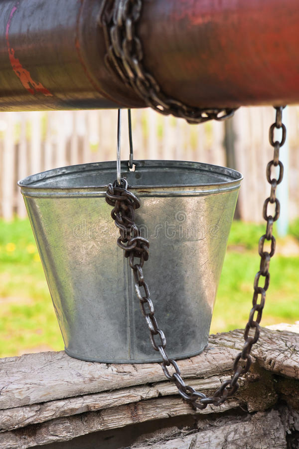 Empty pail, chain and well pulley. Empty pail, old chain and old well pulley stock photos
