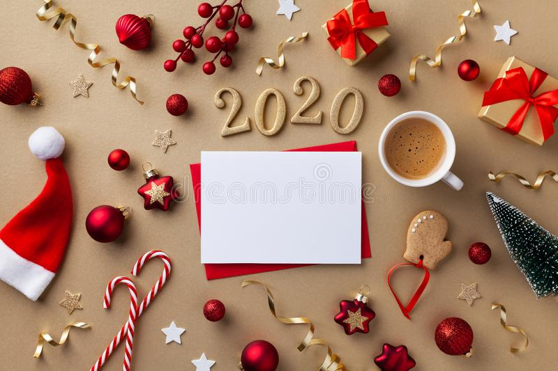 Empty paper blank, cup of coffee and 2020 number for New year greeting card. Gift boxes, holiday decorations on golden background. Top view. Flat lay royalty free stock images
