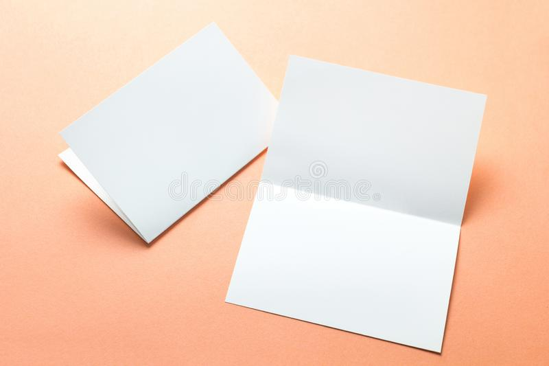 Empty paper flyers, business cards, brochures on an orange background, layout.  stock photos