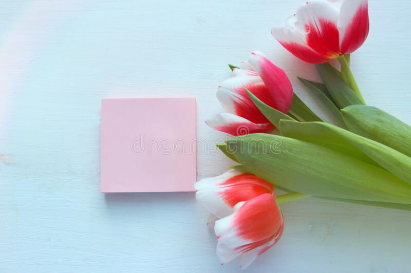 An empty paper note with a red heart-shaped decoration on a white background of a wooden table, a bouquet of tulips. stock photography