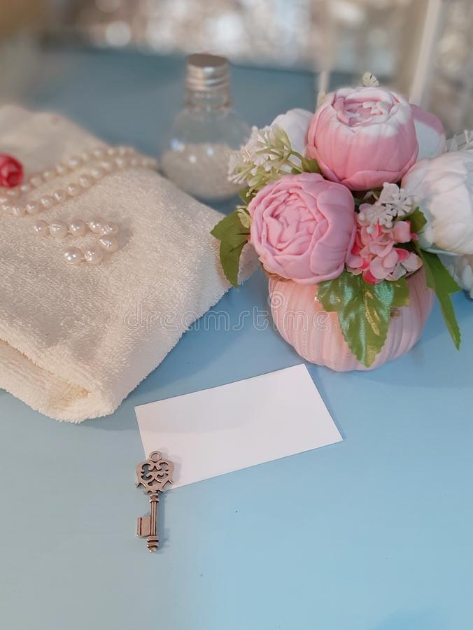 Empty paper tag, silver key, bouquet of flowers and towel on blue background. Blank white greeting card, silver key, bouquet of soap flowers and towel on blue stock image