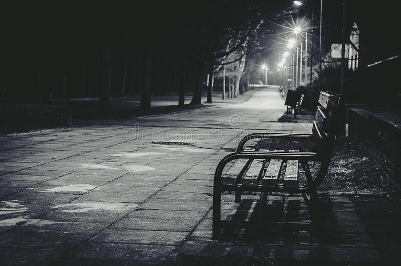 Empty park bench at night stock photography