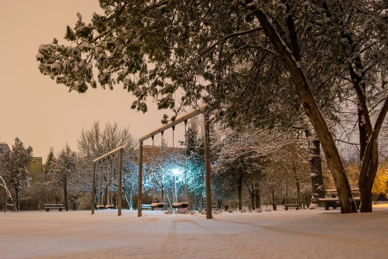 Empty park swings during a Winter night, after a few snow heavy hours. Quiet outdoor place in Bucharest, Romania. With snow covered trees and diffused street stock photo