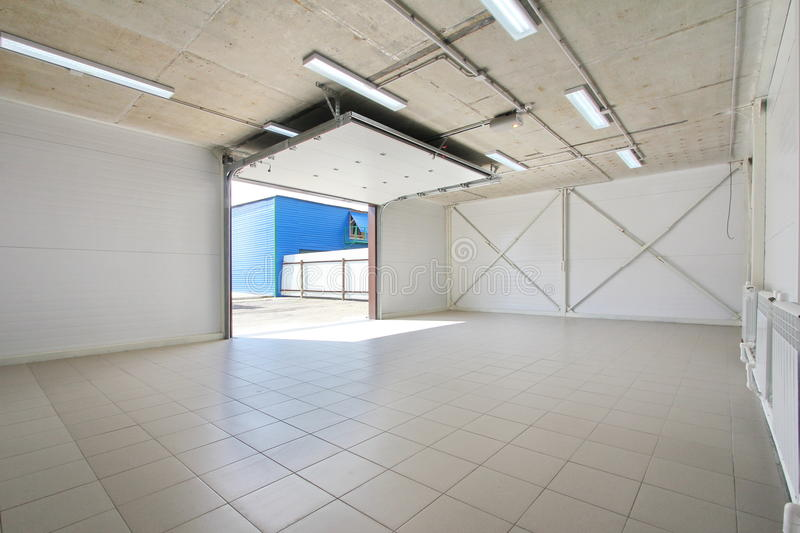 Empty parking garage, warehouse interior with large white gates and gray tile floor. Empty light parking garage, warehouse interior with large white gates and stock photos