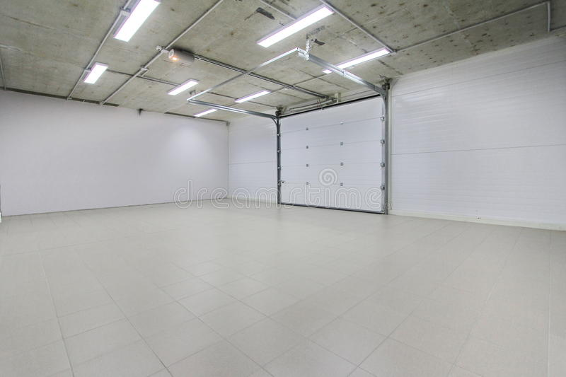 Empty parking garage, warehouse interior with large white gates and gray tile floor. Empty light parking garage, warehouse interior with large white gates and royalty free stock image