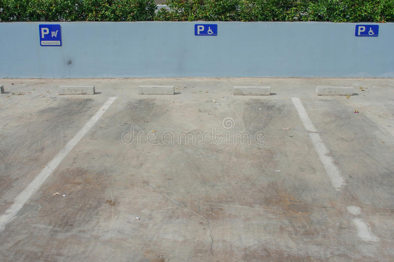 Empty parking space for cripple. Foreign text on blue signs is meaning `Empty parking space for delivery vehicles royalty free stock image