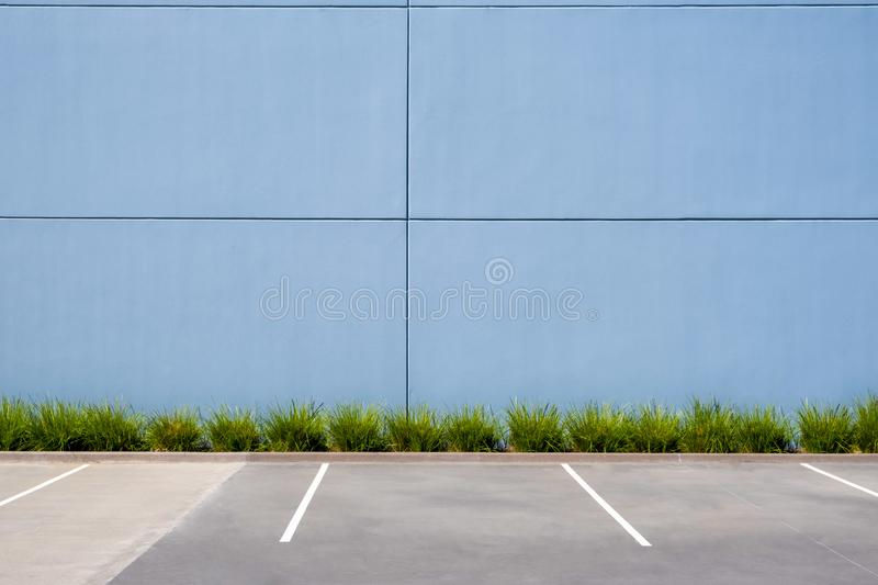 Empty parking spaces against clean concrete wall. Empty parking spaces against clean concrete wall of an industrial building with pach of grass and copy space royalty free stock photography