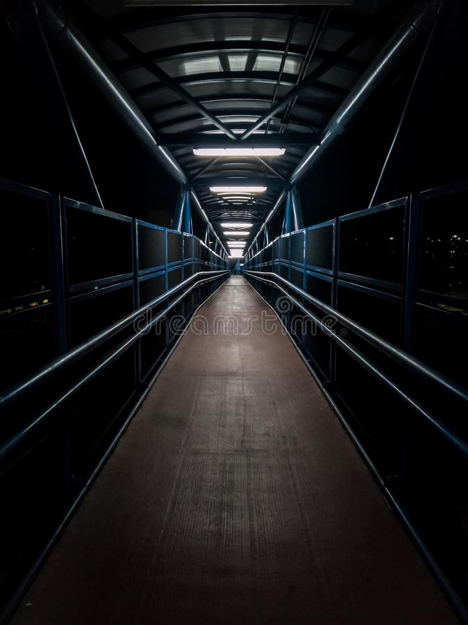 Empty pedestrian walkway illuminated with fluorescent tubes at night. Metallic structure over a road royalty free stock photo