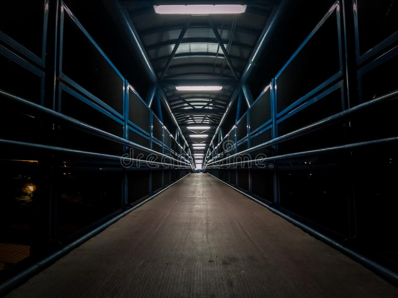Empty pedestrian walkway illuminated with fluorescent tubes at night. Metallic structure over a road stock image