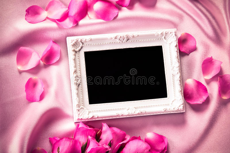Empty photo frame with a bouquet sweet pink roses petal on sof royalty free stock photos