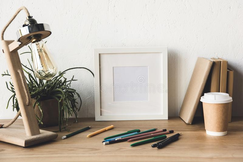 Empty photo frame, plant in flowerpot, table lamp and coffee to go. On wooden table stock images