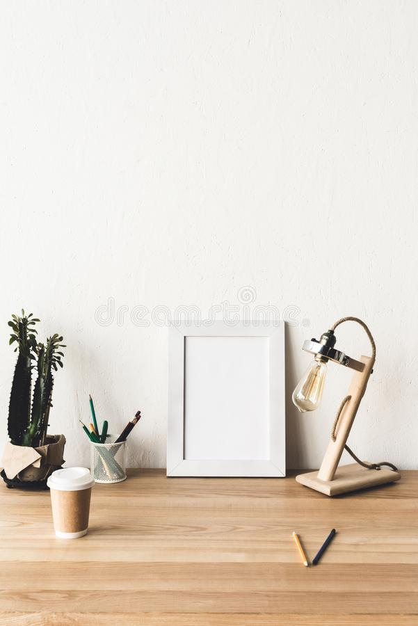 Empty photo frame, plant in flowerpot, table lamp and coffee to go. On wooden table stock image