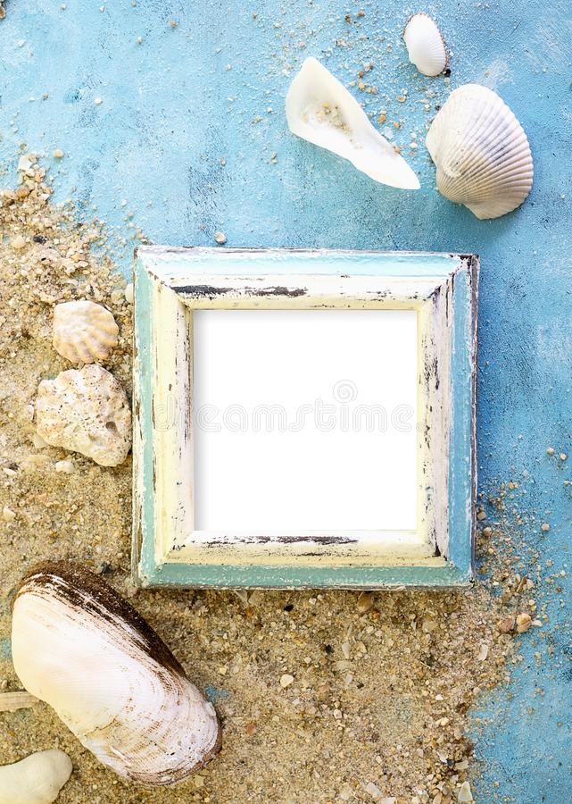 Empty photo frame with sea shells on sand over blue paper. Travel, beach vacation concept royalty free stock image