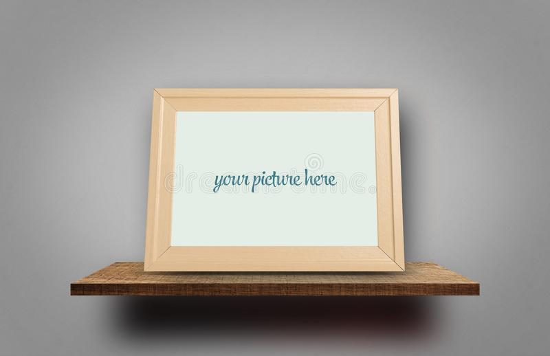 Empty photo frame on wooden shelf on gray background royalty free stock images