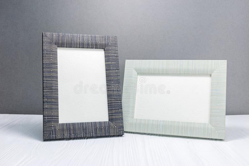 empty photo frames on white wooden desk against grey wall background royalty free stock images