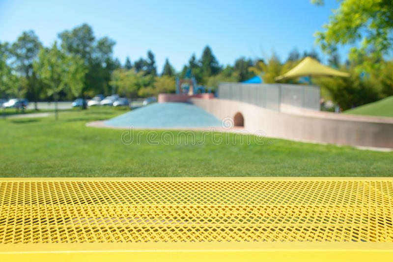 Empty picnic table with blurred playground on background stock photo