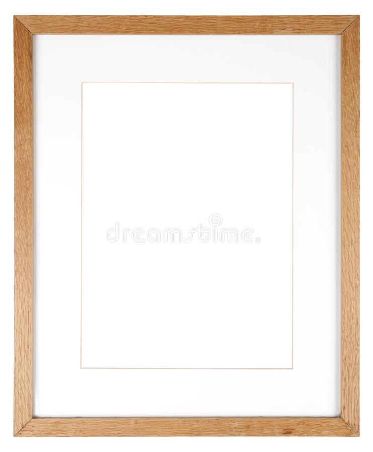 Empty picture frame in a wood grain moulding. Empty picture frame isolated on white in a simple oak wood grain moulding with a mount royalty free stock photo