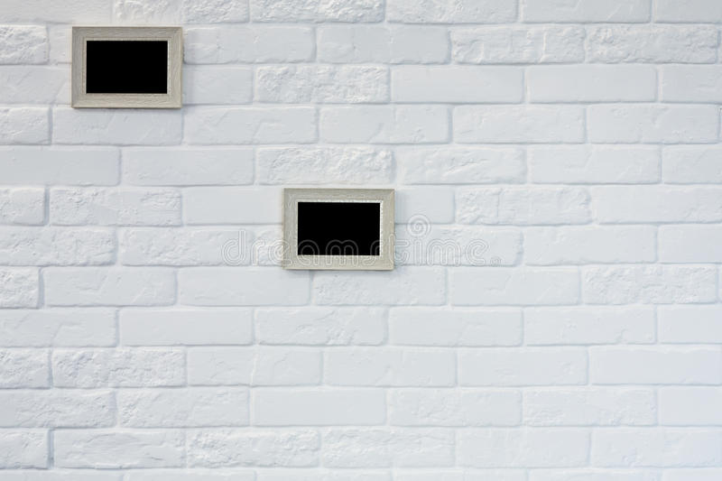 Empty picture frame at white brick wall royalty free stock photography