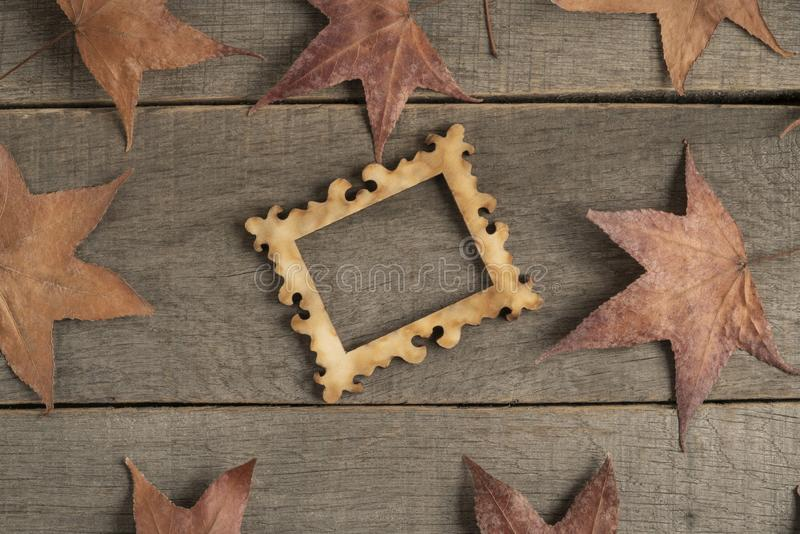Empty picture frame on wooden background decorated with dried autumn leaves stock images