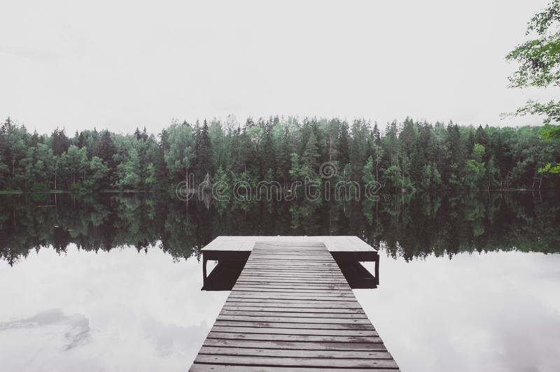 Pier of a beautiful lake, toned, atmospheric photo. The concept of the beauty of nature, peace, loneliness stock photo