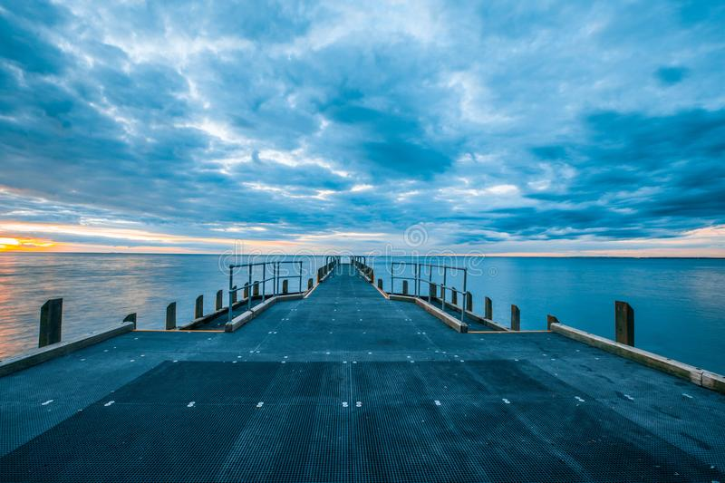 Empty pier and calm bay waters. stock photo