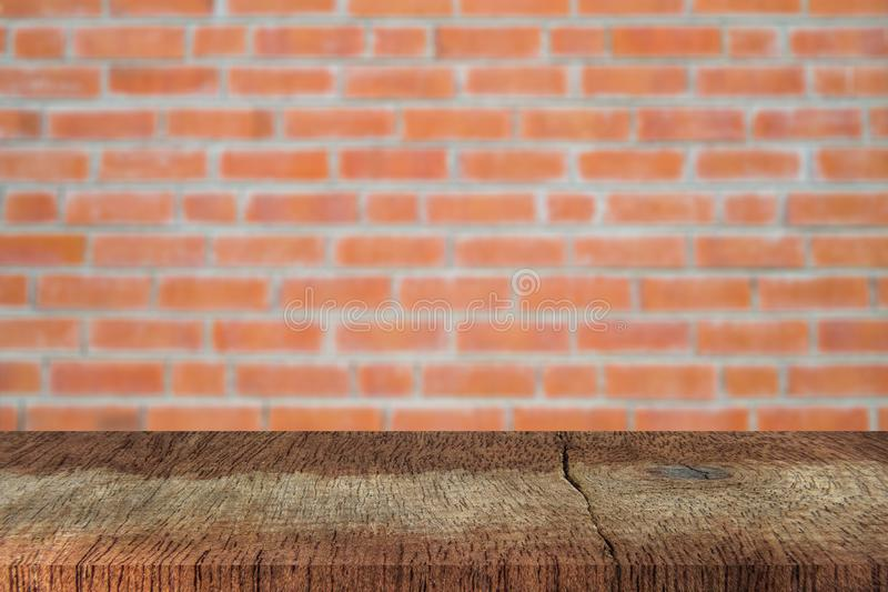 Empty plank brown wood table top with blur red brick wall  texture background. royalty free stock images