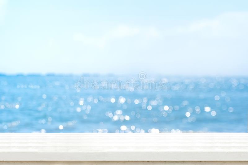 Empty plank white wood table top with blur blue sky and sea boekh background,summer holiday backdrop.Mock up template for display. Or montage of product or royalty free stock photo