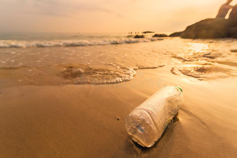 .Empty plastic bottle on the beach with sea waves at morning sunrise.Thailand. Empty plastic bottle on the beach with sea waves at morning sunrise.Thailand royalty free stock photography