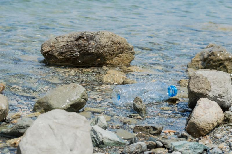 Empty plastic garbage dumped in the water. Empty plastic bottle dumped in the water royalty free stock images