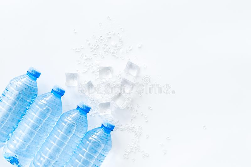 Empty plastic bottles for pure water with ice cubes on white background top view mock up stock images