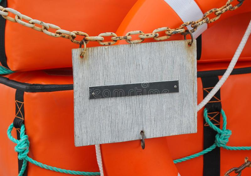An empty plate attached to an old rusty chain in front of an orange life buoy and an orange boat safety kit stock image