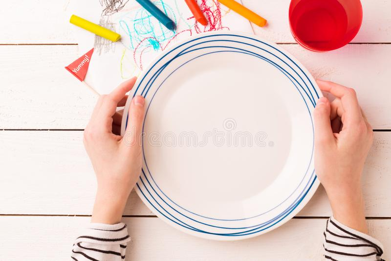 Table setting for kids - empty plate in child`s hands stock photo