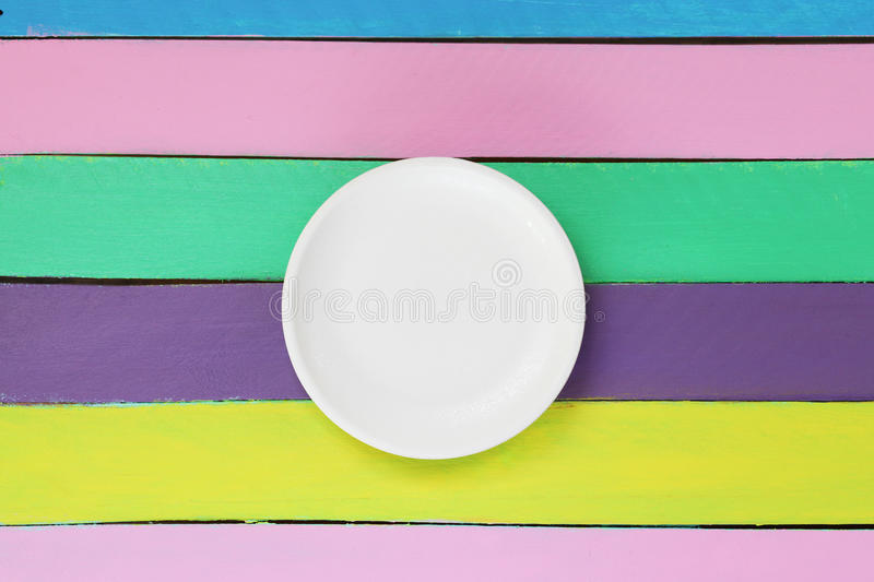 Empty plate on colourful wooden table stock images