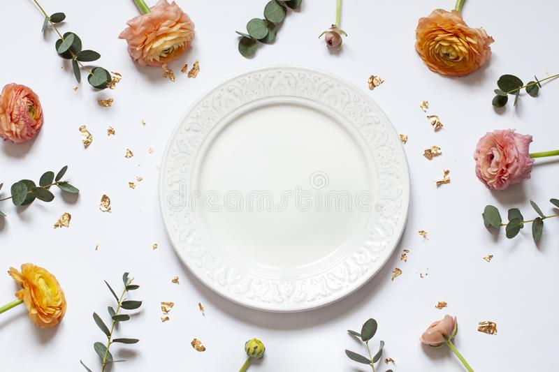Empty plate concept flat lay with floral decorations on the white backdround. Top view. Valentines day, Mothers day or Easter card. Copy space stock photos