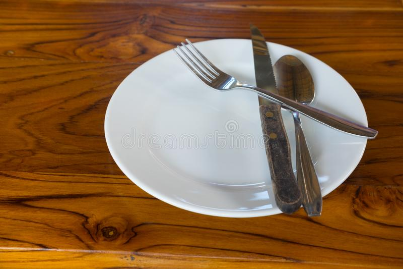 Empty plate with crossed fork and knife royalty free stock images