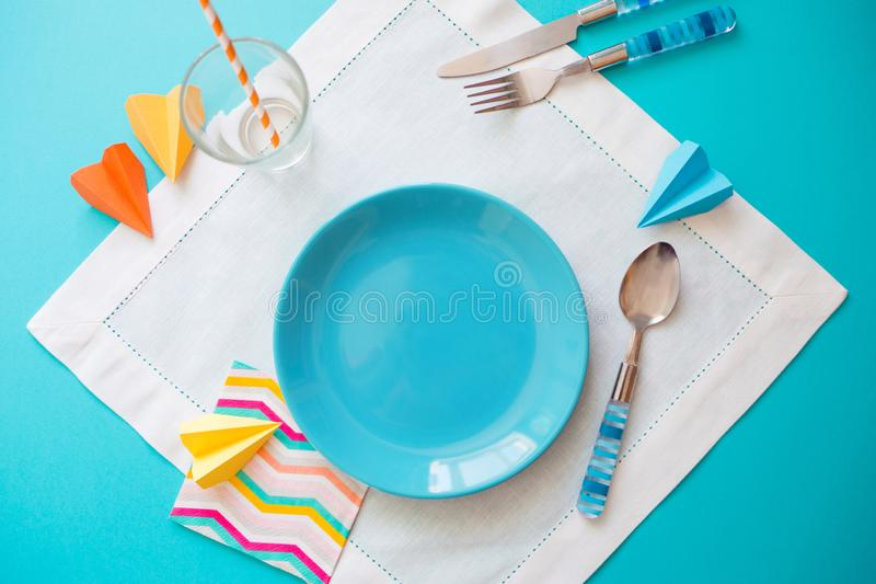 Empty plate and Cutlery on white blue background. concept of kids menu of a cafe or restaurant royalty free stock photos