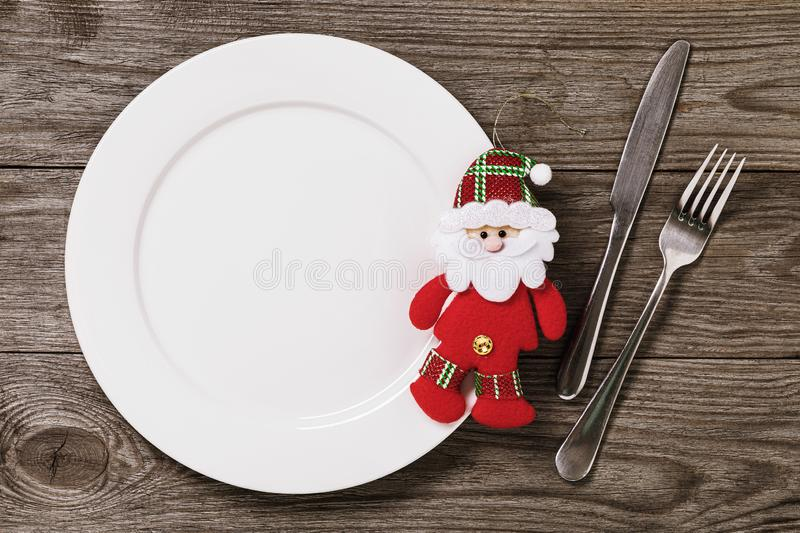 Empty plate and cutlery on a wooden table with copy space. Soft Christmas toy Santa Claus. Food background. Empty plate and cutlery on a wooden table with copy royalty free stock image