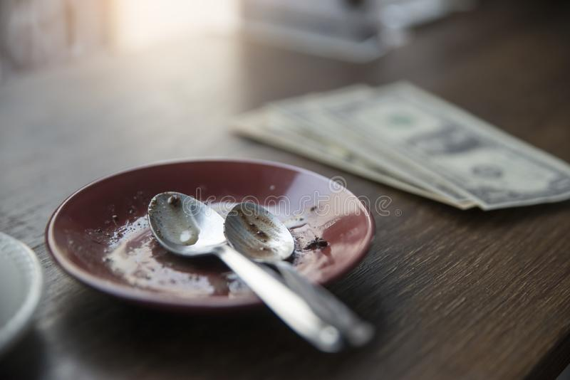 Empty plate dirty plate with cake after eating with dollar money,place on wooden table in coffee shop.Check bill and and tip stock photos