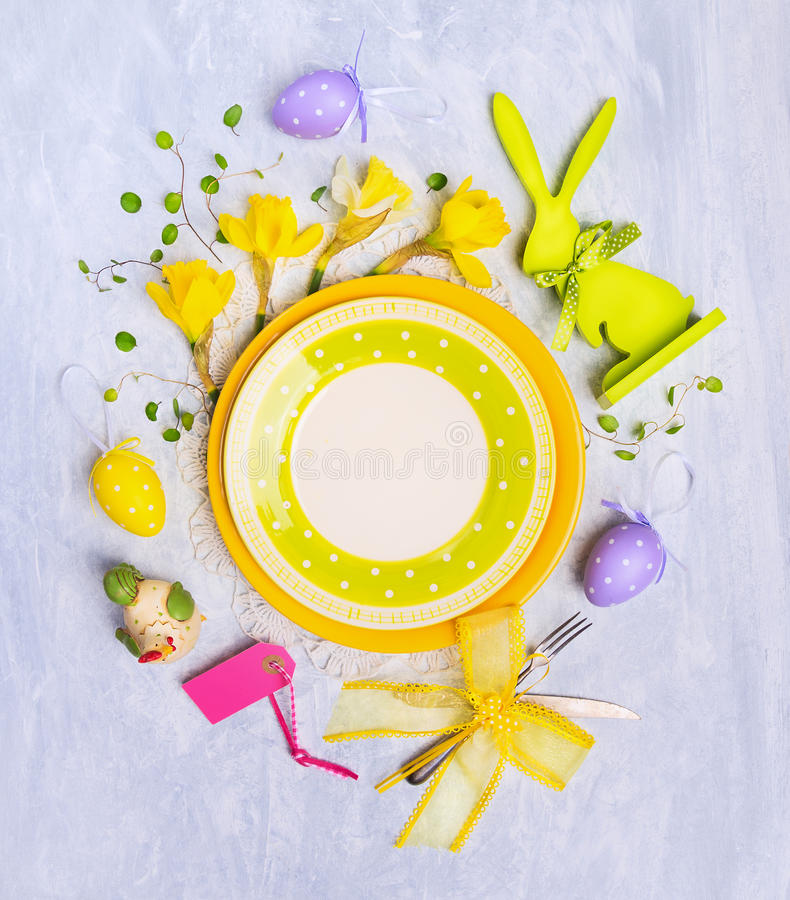 Empty plate with easter egg decoration, sign and flowers on gray wooden background, top view royalty free stock images