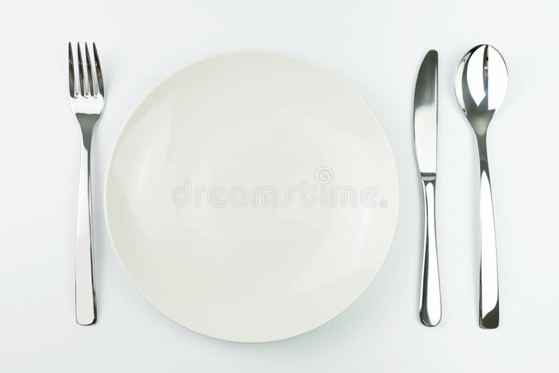 Empty plate with fork, knife and spoon. Empty white dinner plate with stainless steel fork, knife and spoon royalty free stock images