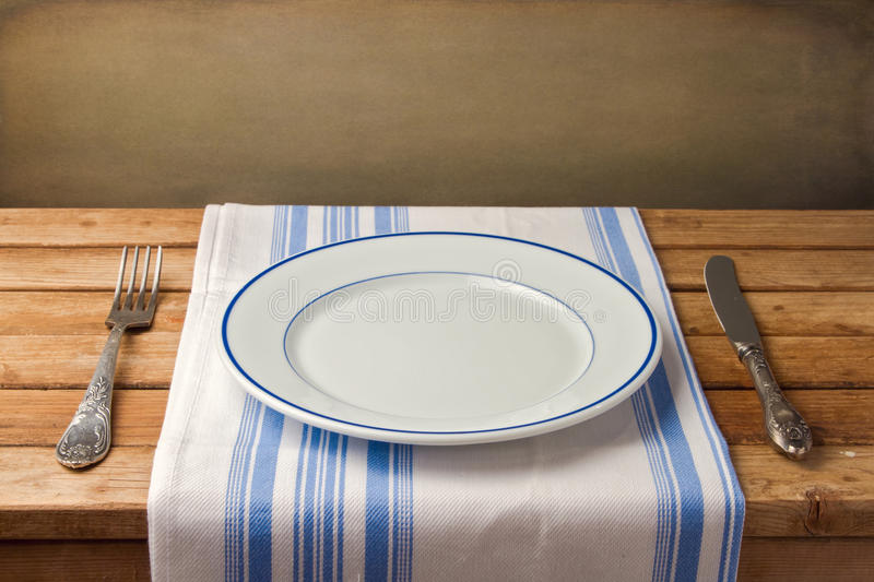 Empty plate with fork and knife on tablecloth. On wooden table over grunge background stock photography